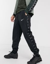 Nike woven taping cuffed joggers in black